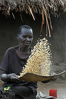 Akulo Hirin winnows maize in front of her hut in Agwang Camp in Lira District in Northern Uganda. While many neighbors have returned to their villages in the wake of a September 2006 ceasefire in the Northern Uganda conflict, she is alone and unable to rebuild a home in her village by herself.  The conflict with the Lord's Resistance Army had forced as many as two million people into camps across northern districts for as many as 20 years. The LRA and Ugandan government have  observed a ceasefire while engaged in peace talks to end the conflict. As a result many residents of camps for the internally displaced have been slowly returning to their villlages to begin again.  (Rick D'Elia)