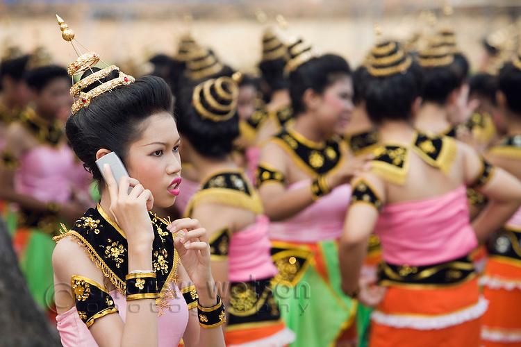 A Thai dancer in colourful costume speaks on her cellphone during the festival of Loi Krathong in Sukhothai Historical Park.  Sukhothai, Sukhothai province, THAILAND