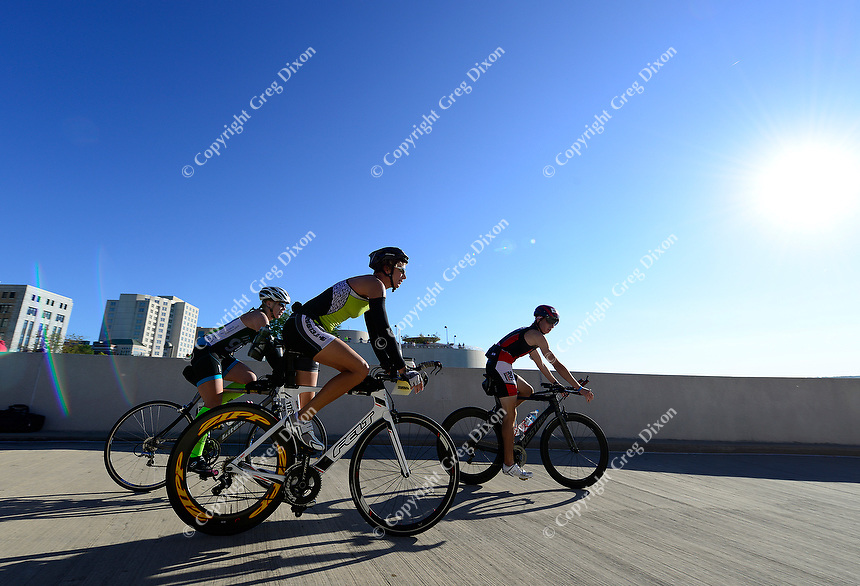Chicago's Kristan Huenink, Omaha's Gina Samland, and Danville, PA's John Hannon (L-R) bike down the ramp of Monona Terrace during the Wisconsin Ironman on Sunday in Madison