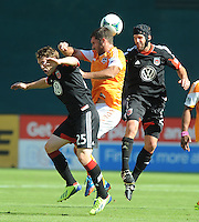 Will Bruin (12) of the Houston Dynamo heads the ball against Jarred Jeffrey (25) and Daniel Woolard (21) of D.C. United. The Houston Dynamo defeated D.C. United 2-1, at RFK Stadium, Saturday October 27, 2013.