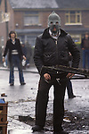 Ireland The Troubles. Belfast 1980s. IRA man in hood during riot.