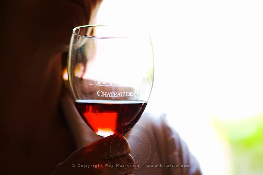 A woman holding in her hand a glass of rose clairet wine with Chateau de Haux emblazoned on the glass, backlit Chateau de Haux Premieres Cotes de Bordeaux Entre-deux-Mers Bordeaux Gironde Aquitaine France