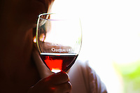 A woman holding in her hand a glass of rose clairet wine with Chateau de Haux emblazoned on the glass, backlit Chateau de Haux Premieres Cotes de Bordeaux Entre-deux-Mers Bordeaux Gironde Aquitaine France