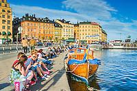 Ungdomar sitter vid en kaj bredvid en träbåt vid Slussen i Stockholm