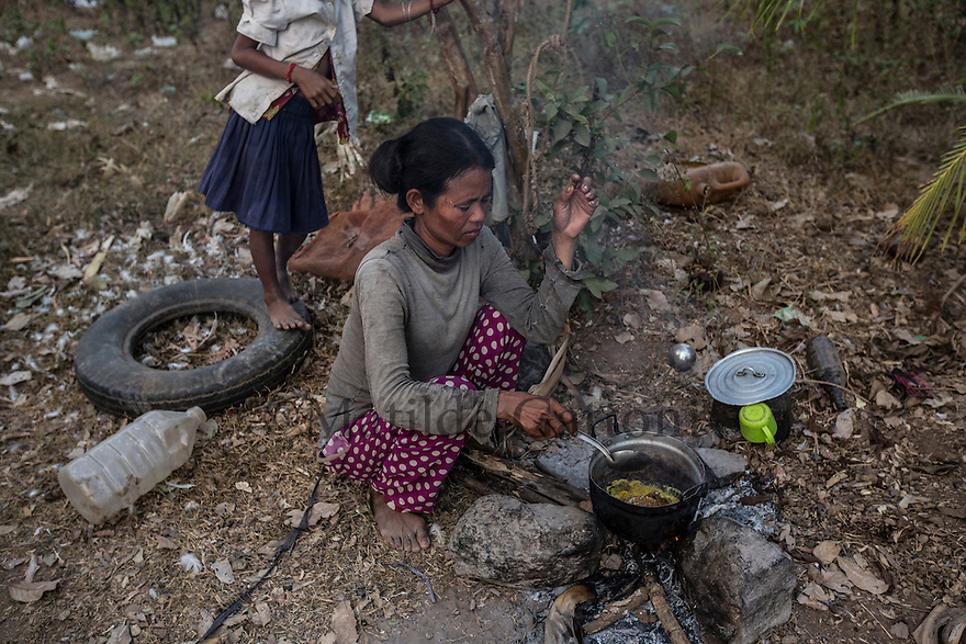 """Cambodia - Kampong Speu Province - Louv Veoun, 39, cooking a piece of royal jelly she found in the woods close to the sugarcane plantation where she works. The family can afford to eat only a handful of rice per day, this royal jelly is a precious find. """"I don't want money, I want my old land back. It is the land of my ancestors"""". Louv Veoun, 39 and mother of 8, was living in a small cottage on her rice field in Kork until March 2010, when she was dispossesed of her two hectares of land and compensated with 25 USD. She was forced to abandon her house and settle in a piece of land belonging to some of her relatives, close to the plantation. Today, she lives in utter poverty together with her family."""