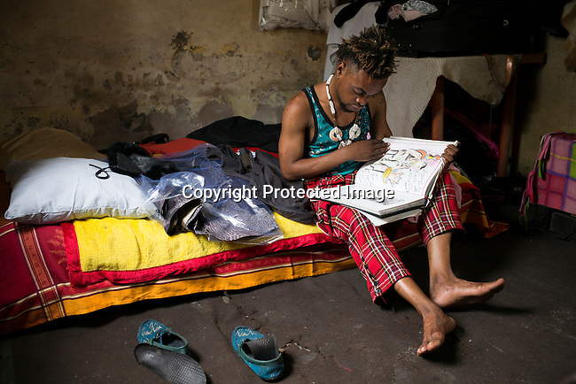 "KINSHASA, DEMOCRATIC REPUBLIC OF CONGO - OCTOBER 3: Mzee Kindingu, the leader of the Sapeurs group The Leopards reads in a fashion book in his bedroom on February 3, 2015 in Kinshasa, DRC. The word Sapeur comes from SAPE, a French acronym for Société des Ambianceurs et Persons Élégants. or Society of Revellers and Elegant People. and it also means, .to dress with elegance and style"". Most of the young Sapeurs are unemployed, poor and live in harsh conditions in Kinshasa, a city of about 10 million people. For many of them being a Sapeur means they can escape their daily struggles and dress like fashionable Europeans. Many hustle to build up their expensive collections. Most Sapeurs could never afford to visit Paris, and usually relatives send or bring clothes back to Kinshasa. (Photo by Per-Anders Pettersson)"