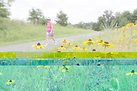 A woman walks past wildflowers. Photo/Andrew Shurtleff Photography, LLC