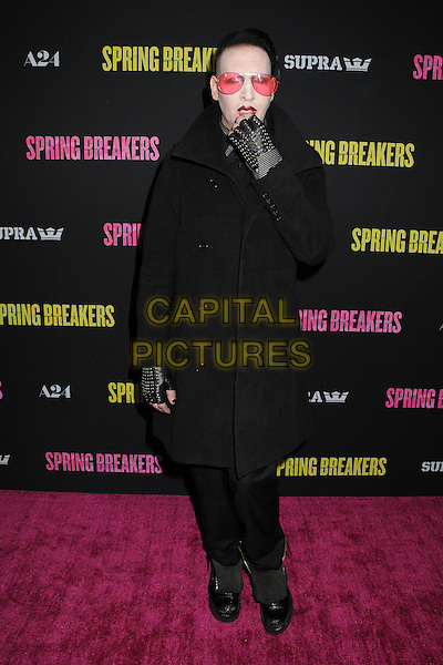 Marilyn Manson (Brian Hugh Warner).At the 'Spring Breakers' Los Angeles Premiere held at Arclight Cinemas, Hollywood, California , USA, .14th March 2013..full length coat  sunglasses tinted pink red lipstick make-up goth black shirt eyeliner studded fingerless gloves hand on over mouth .CAP/ADM/BP.©Byron Purvis/AdMedia/Capital Pictures.