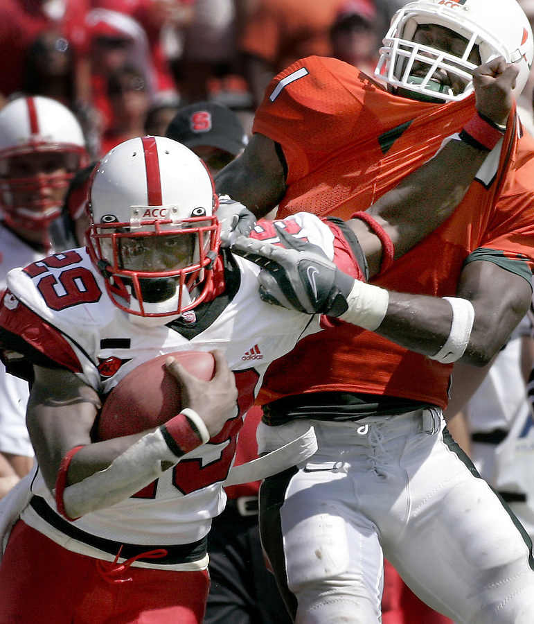 NCSUMIA1b.SP.110307.EDR.JPG  N.C. State's Jamelle Eugene (29) stiff-arms Miami's Kenny Phillips (1) during a rush in the second quarter at the Orange Bowl in Miami, FL, on Saturday, Nov. 3, 2007.  Miami led at halftime 10-7.  Staff photo by Ted Richardson/The News & Observer.