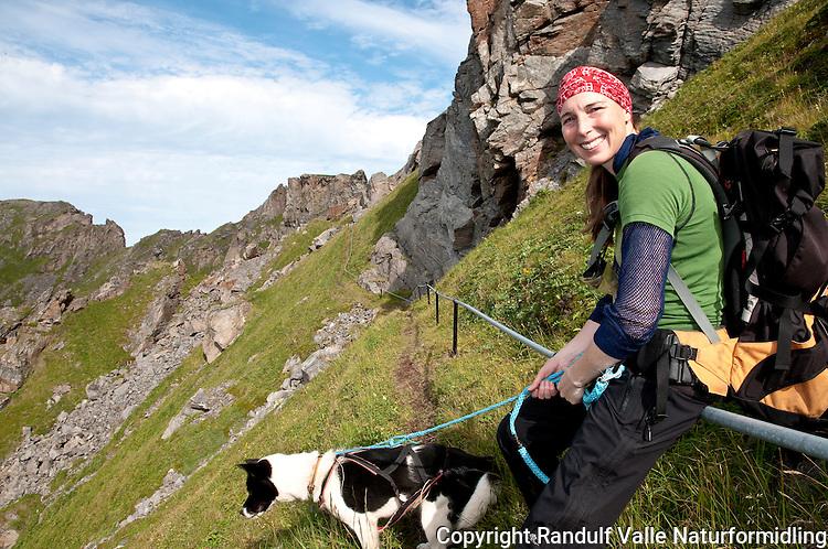 Dame med hund på vei ned Fyrvokterveien til Tarhalsen på Sørøya. ---- Woman and dog walking along steep path.