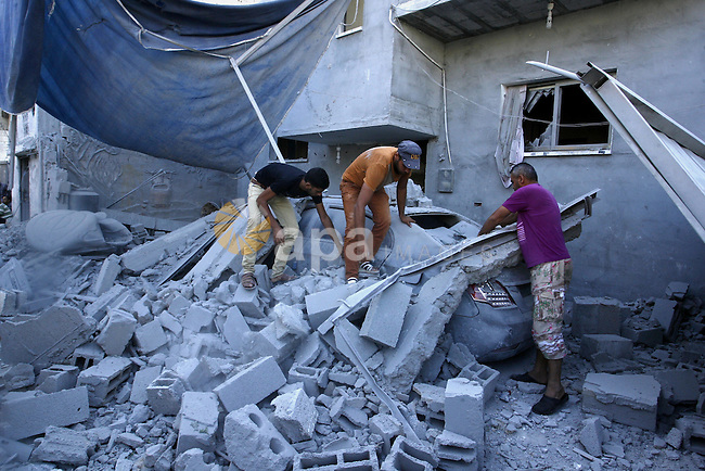Palestinians inspect a house after it was hit by an Israeli military strike in Rafah in the southern Gaza Strip on August 10, 2014. Israel will not engage in talks to end the violence in Gaza while coming under fire, Prime Minister Benjamin Netanyahu said. Photo by Abed Rahim Khatib