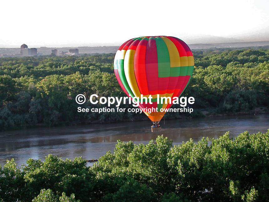 Hot air balloon floats over the Rio Grande. Cottonwood trees line the river for most of its journey through New Mexico. This section of the river is near Albuquerque. 2000091048..Copyright Image from Victor Patterson, 54 Dorchester Park, Belfast, UK, BT9 6RJ..Tel: +44 28 9066 1296.Mob: +44 7802 353836.Voicemail +44 20 8816 7153.Skype: victorpattersonbelfast.Email: victorpatterson@mac.com.Email: victorpatterson@ireland.com (back-up)..IMPORTANT: If you wish to use this image or any other of my images please go to www.victorpatterson.com and click on the Terms & Conditions. Then contact me by email or phone with the reference number(s) of the image(s) concerned.