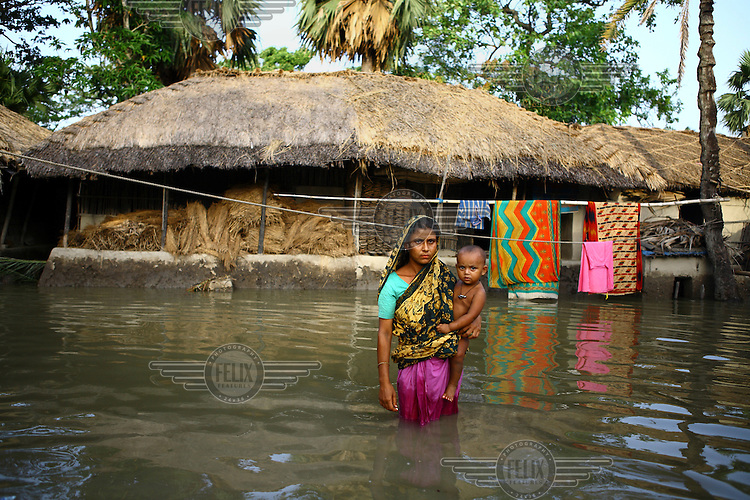 A woman holds her small child in the deep floodwaters in her village. Thousands of people were displaced in Shyamnagar Upazila, Satkhira district after Cyclone Aila struck Bangladesh on 25/05/2009, triggering tidal surges and floods..