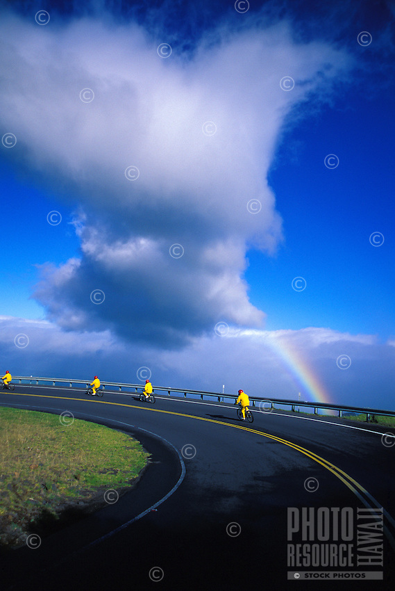 An organized downhill bike tour cruises through the Haleakala Ranch at a 5,000-ft. elevation with a rainbow off the North Shore of Maui.