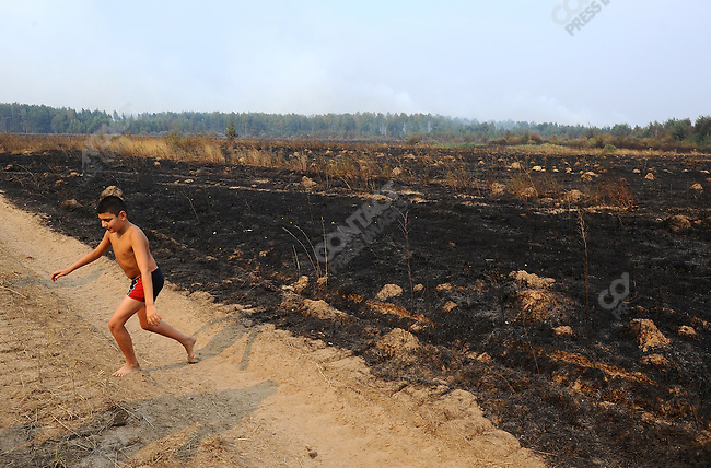 A boy coming back from swimming in a nearby pond walked past a burnt field as volunteers and members of the Emergency Services fought forest fires near the village of Plotava in the east of the Moscow region as fires continued to spread as the unrelenting hot weather continued in central Russia. 05 August 2010