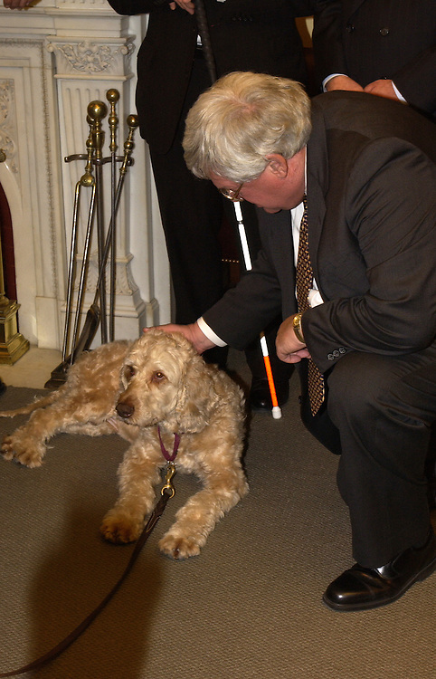 "Speaker of the House Dennis Hastert, R-Ill., gives ""Lancelot"" a pat on the head. The K-9 , who was born blind, was the first dog to have his sight restored through gene therapy. ""Lancelot"" was at the speakers office on behalf of the ""Foundation Fighting Blindness"" to stress the importance of increasing funding to the National Eye Institute in FY 2005."