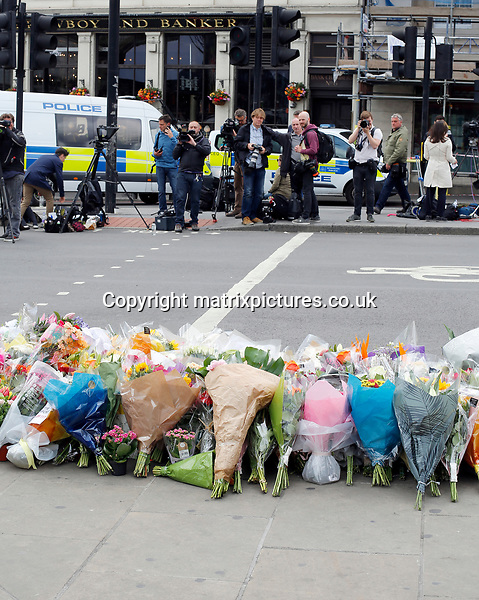 NON EXCLUSIVE PICTURE: MATRIXPICTURES.CO.UK<br /> PLEASE CREDIT ALL USES<br /> <br /> WORLD RIGHTS<br /> <br /> Pictures show flowers being placed and people stopping to pay respect on London Bridge and at The Monument to the Great Fire of London which sits at the end of London Bridge as the city mourns for those affected in the recent terror attack. <br /> <br /> JUNE 6th 2017<br /> <br /> REF: WBD 171155