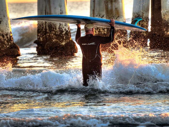 Older surfer hitting the waves near the pier at Cocoa Beach, Florida with the water drops catching the golden morning rays