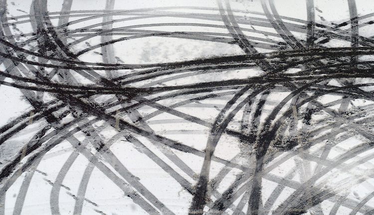 Tire tracks in the snow create an abstract pattern when seen from above.