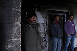 Members of the Hamayel family inspect the damage to their home, that was attacked and burnt by suspected Jewish extremists using petrol bombs, in the village of Abu Falah, northeast of Ramallah, on November 23, 2014. Suspected Jewish extremists firebombed a house in a Palestinian village in the occupied West Bank early, its mayor said, pointing the finger of blame at local settlers. Masud Abu Mura, mayor of Khirbet Abu Falah, said four women were inside the house at the time, but they all escaped unharmed. Photo by Shadi Hatem