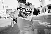 "Nuevo Laredo, Mexico<br /> June 7, 2007<br /> <br /> In Nuevo Laredo, a United States border town, street vendors sell a  paper displaying the days regional drug related execution with the headline, ""Cut Throat"". Drug related executions in the Nuevo Laredo are a daily event."
