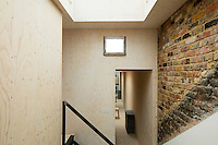A Victorian home has been given a modernist aesthetic. A large skylight was installed above the stairs to illuminate the heart of the house and allows light to penetrate right to the ground floor. Leaving the original brickwork exposed lends a rustic touch whilst the other walls are clad in birch plywood.