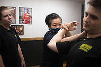 """Meg Austin of Fayetteville (from left) looks on as Diem Ngu demonstrates a silat self-defense maneuver on Corey Mullins of Fort Smith, Saturday, June 20, 2020 at Integrated Combat Systems NWA in Fayetteville. Instructors provided a four hour silat seminar for combat enthusiasts and people interested in self-defense. Silat is an Indonesian form of martial arts involving empty hand combat, grappling and bladed fighting. """"Unlike other martial arts, everything is trained concurrently. You apply the same concepts with empty hands as with weapons. It's a more streamlined process of learning how to fight and defend yourself,"""" said Diem Ngu, owner and instructor. Check out nwaonline.com/200621Daily/ for today's photo gallery. <br /> (NWA Democrat-Gazette/Charlie Kaijo)"""