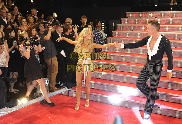 Ola &amp; James Jordan<br /> The red carpet launch for 'Strictly Come Dancing' at Elstree Studios, Borehamwood, England.<br /> September 3rd, 2013<br /> full length gold dress black suit pinstripe trousers dancing holding hands married husband wife <br /> CAP/FIN<br /> &copy;Steve Finn/Capital Pictures