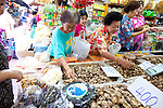Elderly Chinese women shopping for dried mushrooms in Bangkok's Chinatown market.