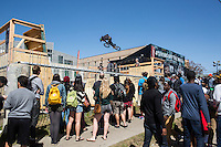 South by Southwest onlookers watch in amazement as BMX riders catch air on a custom competitive BMX half pipe Ramp built for SXSW.