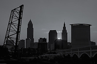 The rising sun peeks over one of the downtown buildings and casts an orange glow in the sky behind the skyline of Cleveland, Ohio