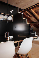 "The wall in this dining room is faced in black linoleum and an open staircase leads to the bedroom above; the dining chairs are the ""Plastic Side Chair"" design by Charles Eames"