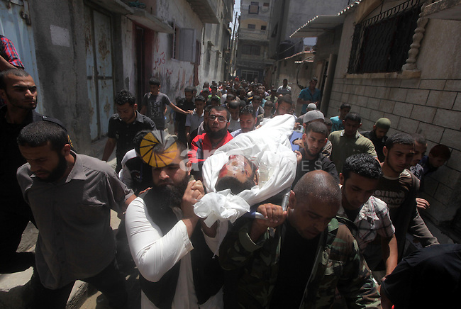 Palestinians mourners carry the body of Haitham Al-Meshal, during his funeral in Gaza City, on April 30, 2013. An Israeli air strike on Gaza City killed one person Palestinian officials said, with Israel saying it targeted a militant involved in a rocket attack on Eilat on April 17. Photo by Ashraf Amra