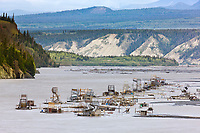 Subsistence use fish wheels along the Copper river catch red and king salmon. Mount Blackburn of the Wrangell mountains in the distance.