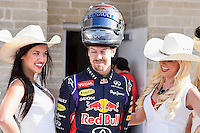 Sebastian Vettel driver of Infiniti Red Bull Racing reacts while making a photograph with COTA girls before 2014 Formula 1 United States Grand Prix race, Sunday, November 02, 2014 in Austin, Tex. (Mo Khursheed/TFV Media via AP Images)