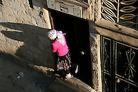 Girl hanging out of doorway in Mardin, southeastern Turkey