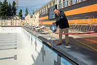 Greg Ochoa, Senior Project Manager, pours a bucket of water from Taylor Pool into the new pool of the De Mandel Aquatic Center at Occidental College, Dec. 12, 2019.<br /> (Photo by Marc Campos, Occidental College Photographer)