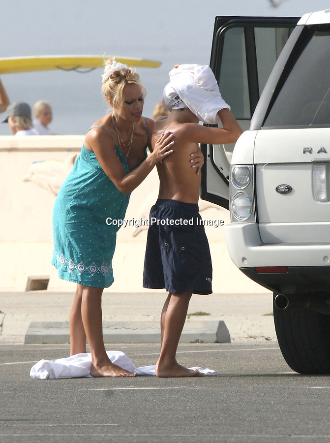 7-24-08.Exclusive.Pamela Anderson walking around bare feet while rubbing sun tan lotion all over her kid at the beach in Malibu California.  Pamela was wearing some crazy black eye liner and didn't seem to care that her panties were in full view. ..AbilityFilms@yahoo.com.805-427-3519.www.AbilityFilms.com.