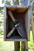 A set of tools is kept in a specially made box nailed to one of the uprights of the enclosed garden area