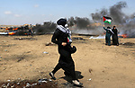 Palestinian women run for cover from tear gas canisters fired by Israeli security forces during clashes in tents protest where Palestinians demanding the right to return to their homeland, at the Israel-Gaza border, in Khan Younis in the southern Gaza Strip, on May 11, 2018. Photo by Ashraf Amra