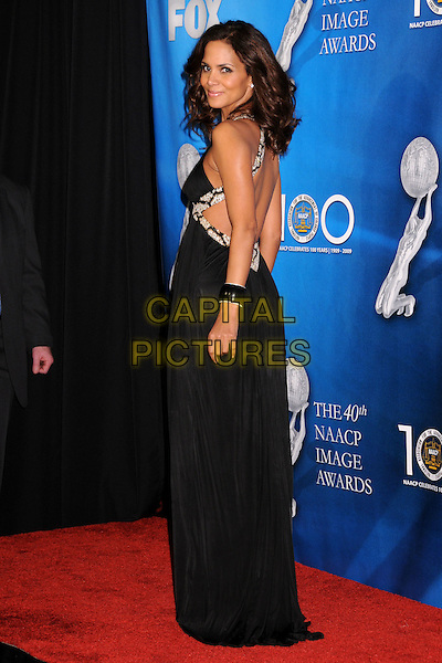 HALLE BERRY.40th Annual NAACP Image Awards - Press Room at the Shrine Auditorium, Los Angeles, California, USA..February 12th, 2009.full length long maxi black dress bracelet looking over shoulder beads beaded cut out away.CAP/ADM/BP.©Byron Purvis/AdMedia/Capital Pictures.