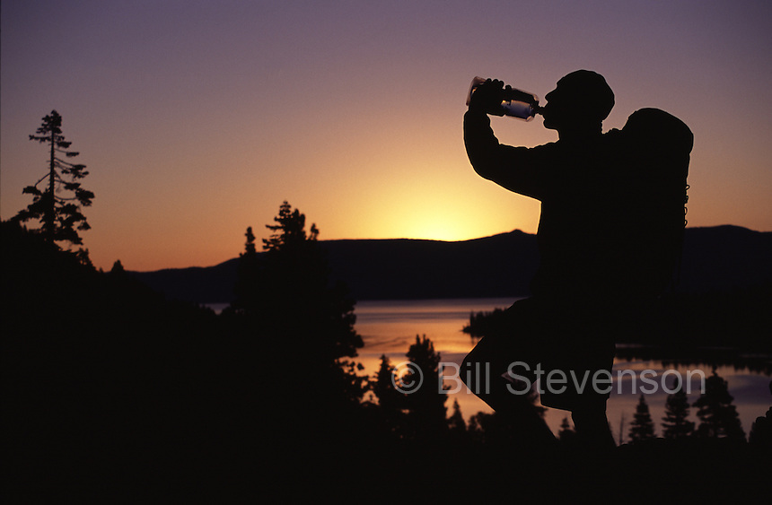 A silhouette of a man drinking water at sunrise above Lake Tahoe