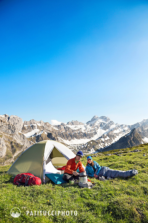 Two people at their tent and campsite using a stove while relaxing after a day of hiking in the Alpstein, Appenzell Region, Switzerland