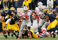 Ohio State Buckeyes running back Ezekiel Elliott (15) runs upfield past Michigan Wolverines safety Delano Hill (44) and linebacker James Ross (15) during the fourth quarter of the NCAA football game at Michigan Stadium in Ann Arbor on Nov. 28, 2015. Ohio State won 42-13. (Adam Cairns / The Columbus Dispatch)
