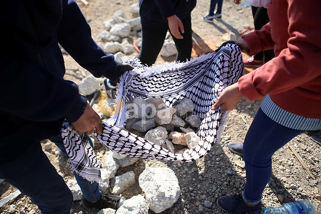 Palestinian female protesters gather stones during clashes with Israeli security forces near the Jewish settlement of Bet El, near the West Bank city of Ramallah, on October 14, 2015. Seven Israelis and 30 Palestinians, including children and assailants, have been killed in two weeks of bloodshed in Israel, Jerusalem and the occupied West Bank. The violence has been partly triggered by Palestinians' anger over what they see as increased Jewish encroachment on Jerusalem's Al-Aqsa mosque compound. Photo by Shadi Hatem