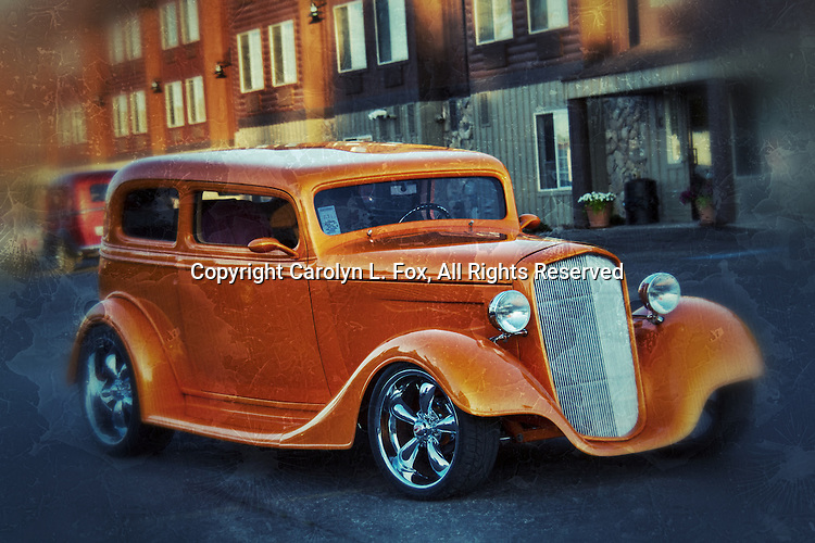 An old orange car sits next to a hotel.