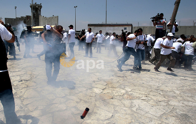Israeli soldiers attack Palestinian journalists during a demonstration demanding for the free movement of journalists and Palestinians at the Qalandia checkpoint between Ramallah and Jerusalem, in the occupied West Bank on July 17, 2013. Photo by Nedal Eshtayah
