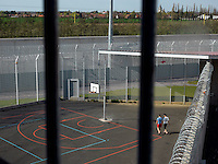 Inmates in an exercise yard at the Detention Centre of the Centre Penitentiaire de Lille-Annoeullin. In the background is the city of Annoeullin.