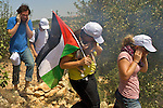 International activists flee after Israeli soldiers attacked without provocation using concussion grenades & CS gas during a non-violent demonstration in the West Bank village of Beit Ummar near Hebron on 10/07/2010.