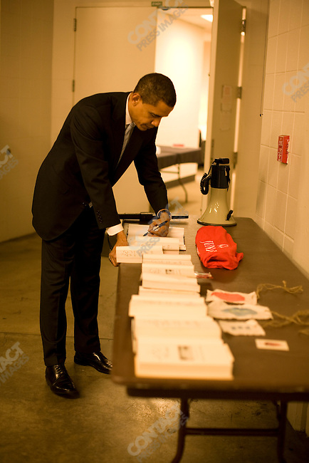 """Senator Barack Obama, Democratic presidential candidate, signs books backstage before a campaign speech at the """"Key Arena"""" in the Seattle Center, Seattle, Washington, February 7, 2008."""